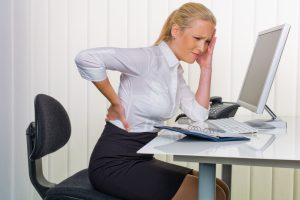 women in the office with back pain